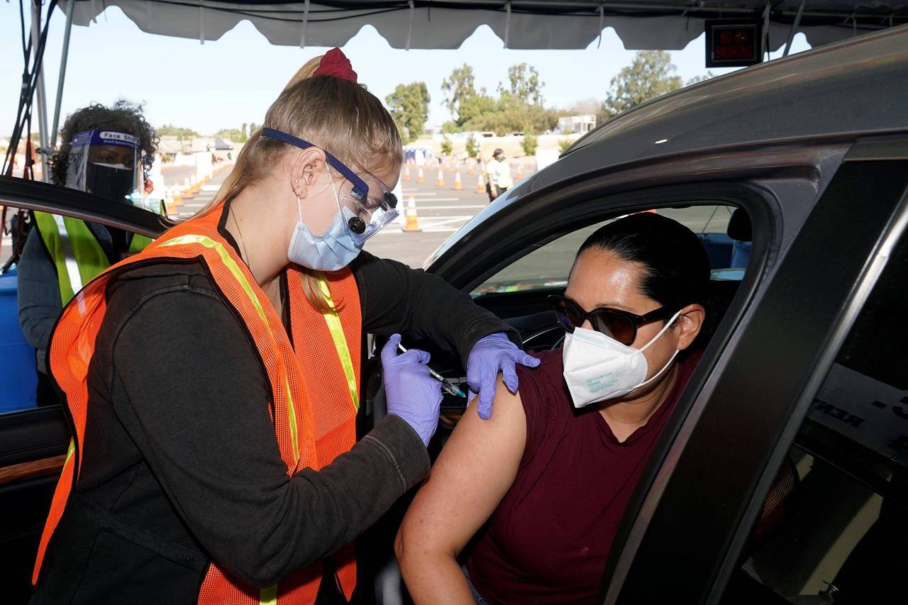 FILE - In this March 2, 2021, file photo, Vanessa Guerra, at right, a special education teacher at Grant Elementary School in Hollywood, receives a shot of the Moderna COVID-19 vaccine from nurse Kelly Mendoza at a site for employees of the Los Angeles school district in the parking lot of SOFI Stadium in Inglewood, Calif. Cities and states are rapidly expanding access to vaccines as the nation races to head off a resurgence in coronavirus infections and reopen schools and businesses battered by the pandemic. (AP Photo/Marcio Jose Sanchez, File)